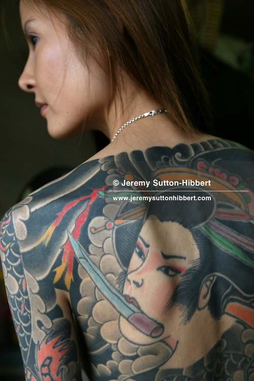 Shoko Tendo reveals her Yakuza style tattoos, including a large depiction of the Muromachi-period courtesan Jigoku Dayu (with a dagger clenched in her teeth) on her back, in the house of her sister Maki, in Honjo near Tokyo, Japan, Saturday, Sept. 1st, 2007. Shoko Tendo, daughter of Yakuza boss Hiroyasu Tendo (now deceased) has written an autobiographical book - 'Yakuza Moon',  describing her life growing up with a Yakuza criminal boss for a father, of her addiction to drugs, and the failed, and often violent sexual relationships she had with men. Shoko Tendo has a body covered in Yakuza style tattoos, including a large depiction of the Muromachi-period courtesan Jigoku Dayu (with a dagger clenched in her teeth), on her back. Shoko Tendo now lives in Tokyo with her 2 year old daughter Komachi.