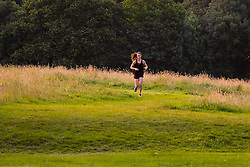 Hampstead Heath, London, July 20th 2016. A woman runs through Hampstead Heath as the first rays of the sun illuminate the grass as London prepares for another hot summer's day. &copy;Paul Davey<br /> FOR LICENCING CONTACT: Paul Davey +44 (0) 7966 016 296 paul@pauldaveycreative.co.uk