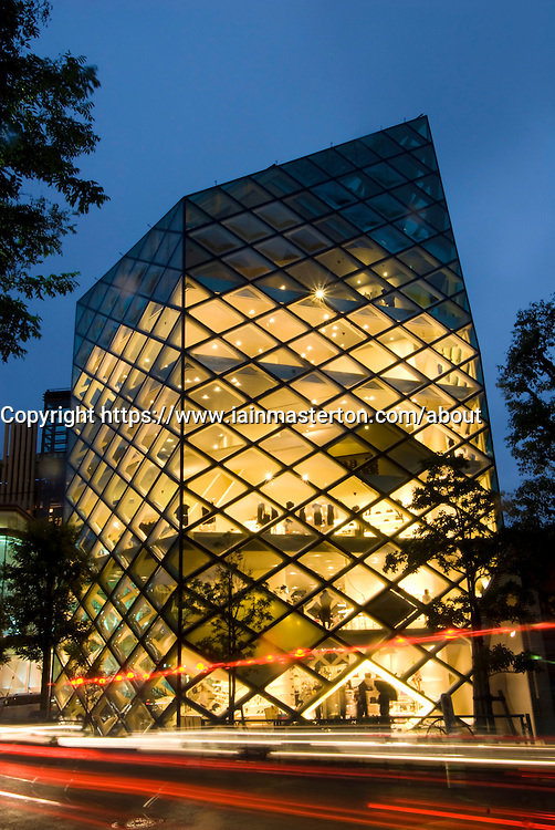 Night view of illuminated glass walled Prada luxury store in central Tokyo Japan