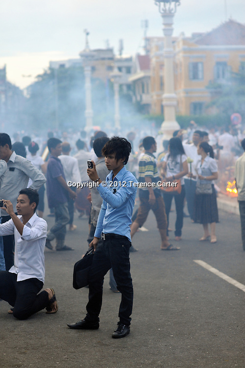 A mourner take a photo to remember the day when King Father Norodom Sihanouk's body was returned to the Royal Palace, Phnom Penh, starting a week of mourning in Cambodia.