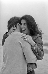 woman enjoying a hug by a man on the beach