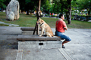 A Kaohsiung resident and his best friend take time out in a park next to the Love River.