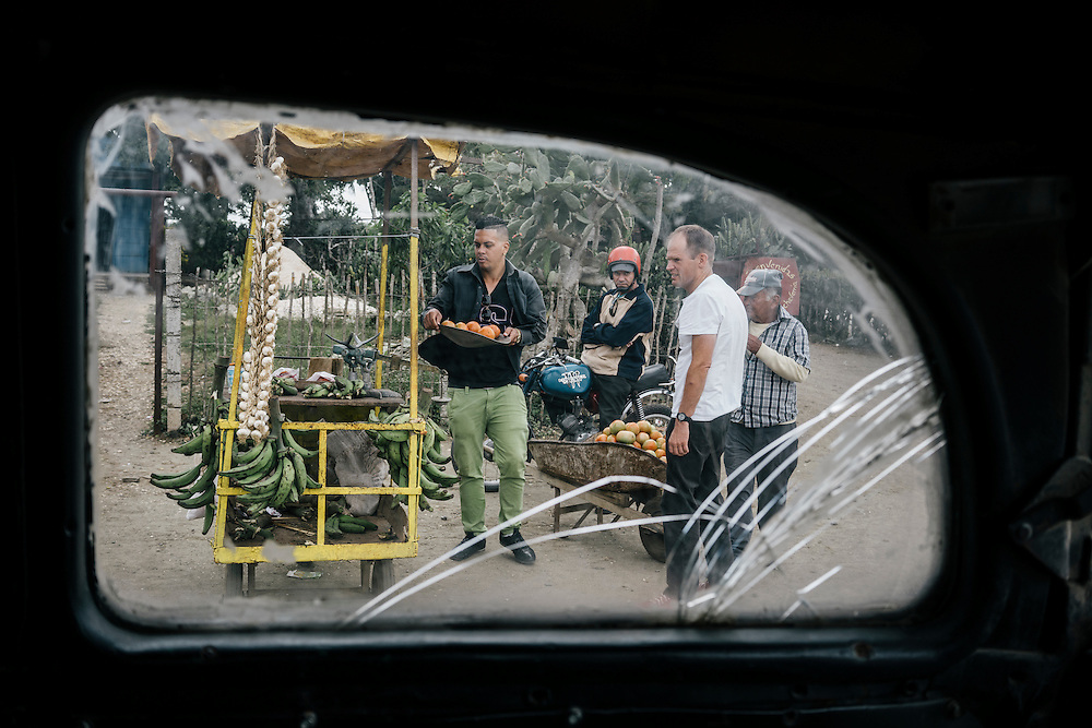 Ornithologist Martjan Lammertink, center, buys food supplies from a roadside cart on the way toward Farallones in Eastern Cuba to search for the Ivory-billed woodpecker on Jan 24, 2016.