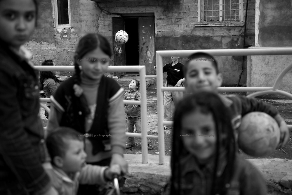"""Kids playing on a street. This image is part of the photoproject """"The Twentieth Spring"""", a portrait of caucasian town Shushi 20 years after its so called """"Liberation"""" by armenian fighters. In its more than two centuries old history Shushi was ruled by different powers like armeniens, persians, russian or aseris. In 1991 a fierce battle for Karabakhs independence from Azerbaijan began. During the breakdown of Sowjet Union armenians didn´t want to stay within the Republic of Azerbaijan anymore. 1992 armenians manage to takeover """"ancient armenian Shushi"""" and pushed out remained aseris forces which had operate a rocket base there. Since then Shushi became an """"armenian town"""" again. Today, 20 yeras after statement of Karabakhs independence Shushi tries to find it´s opportunities for it´s future. The less populated town is still affected by devastation and ruins by it´s violent history. Life is mostly a daily struggle for the inhabitants to get expenses covered, caused by a lack of jobs and almost no perspective for a sustainable economic development. Shushi depends on donations by diaspora armenians. On the other hand those donations have made it possible to rebuild a cultural centre, recover new asphalt roads and other infrastructure. 20 years after Shushis fall into armenian hands Babies get born and people won´t never be under aseris rule again. The bloody early 1990´s civil war has moved into the trenches of the frontline 20 kilometer away from Shushi where it stuck since 1994. The karabakh conflict is still not solved and could turn to an open war every day. Nonetheless life goes on on the south caucasian rocky tip above mountainious region of Karabakh where Shushi enthrones ever since centuries."""