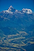Aerial photograph of Machapuchare (6,993 meters), also known as the Fish Tail Mountain, and one of the peaks of the Annapurna Range rising above green valleys near Pokhara Nepal.