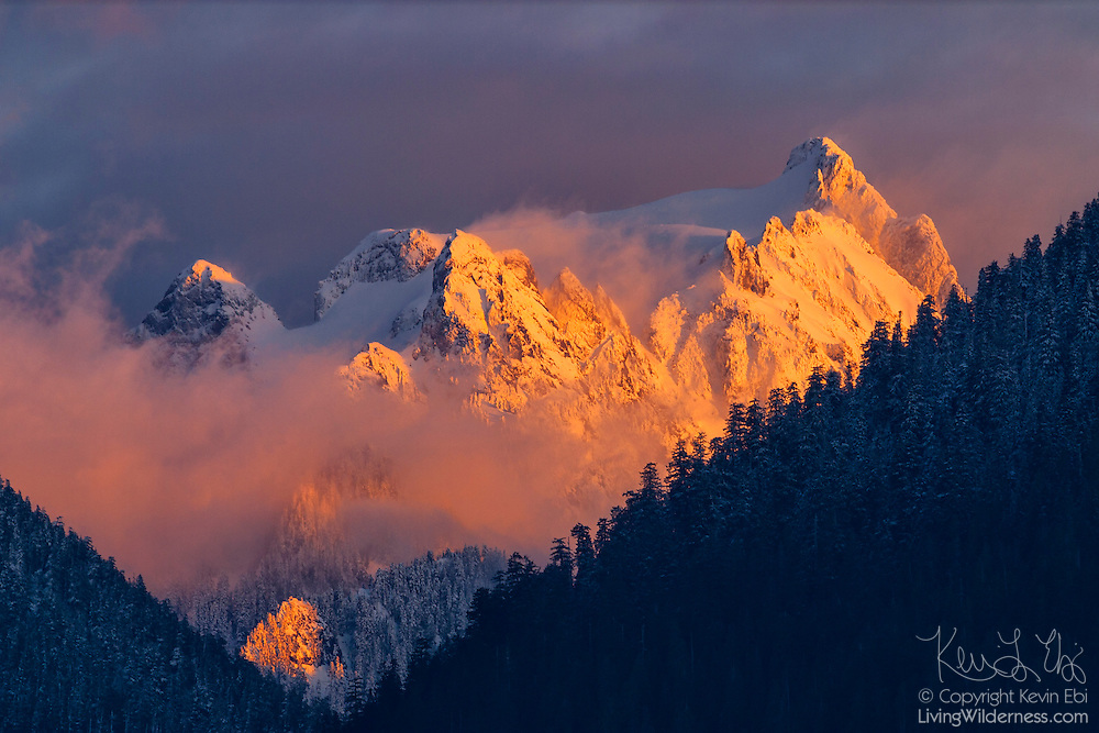 A winter storm partially obscures Whitehorse Mountain, a 6840 foot (2085 meter) peak in the North Cascades of washington state. The steep peak is located near the town of Darrington.