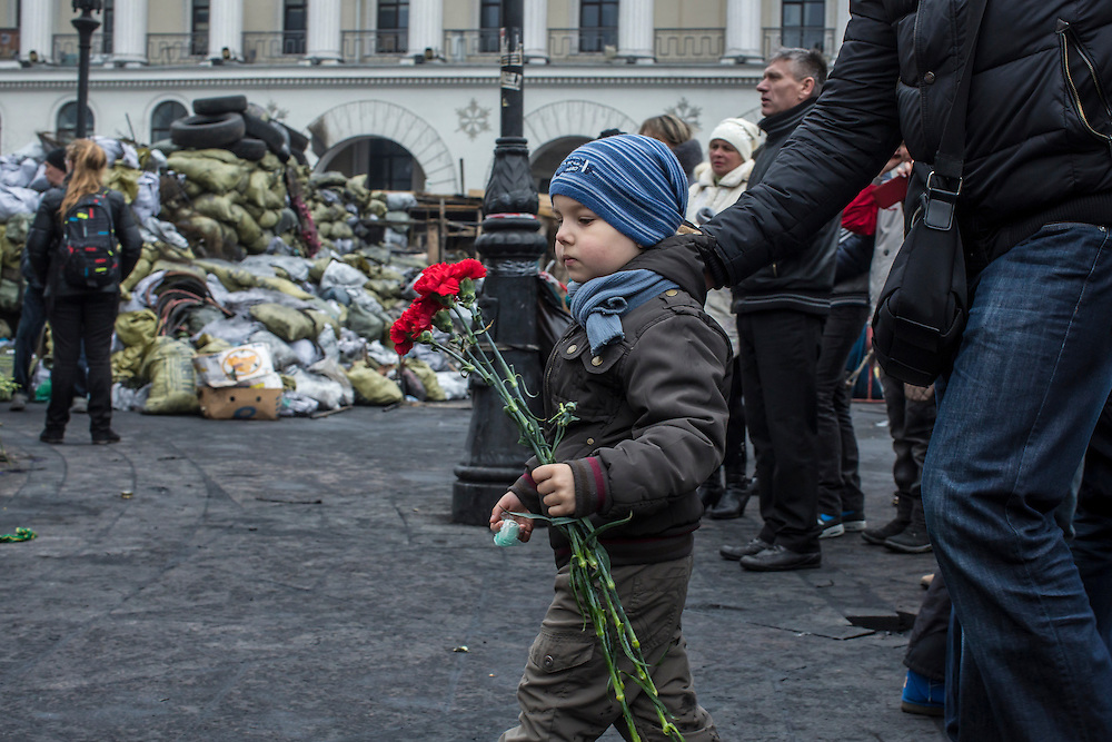 KIEV, UKRAINE - FEBRUARY 23: A boy carries flowers to place at a memorial to anti-government protesters killed in chashes with police on Independence Square on February 23, 2014 in Kiev, Ukraine. After a chaotic and violent week, Viktor Yanukovych has been ousted as President as the Ukrainian parliament moves forward with scheduling new elections and establishing a caretaker government. (Photo by Brendan Hoffman/Getty Images) *** Local Caption ***