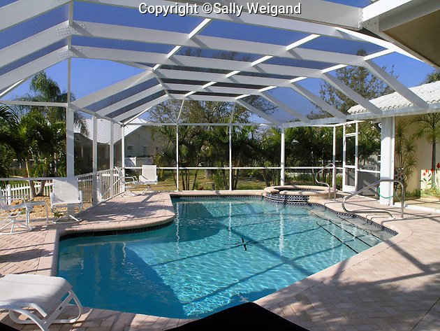 Freeform pool lanai furniture pool deck of pavers for Florida lanai