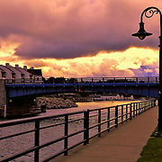 &quot;Drawbridge at Charlevoix&quot;<br /> <br /> Sky drama, sunlight and clouds in the early morning along the walkway in Charlevoix Michigan heading towards the drawbridge.
