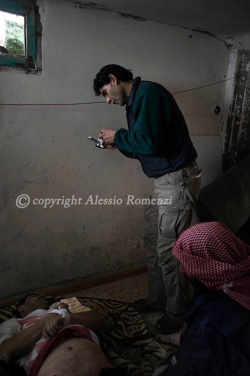 SYRIA - Al Qsair. A Syrian reporter as he arrived to the place where people brought the body of a man shot dead by a Syrian Army's sniper  in Al Qsair, on January 29,  2012. Al Qsair is a small town of 40000 inhabitants, located 25Km south-west of Homs. The town is besieged since the beginning of November and so far it counts 65 dead.In all Syria there are hundreds of non-professional reporters who without experience and without proper gear keep documenting, day after day, the crackdown of the regime. This series of pictures is dedicated to them... to this colleagues who among every kind of difficulties and risks let know to the word their stories and drama.  ALESSIO ROMENZI