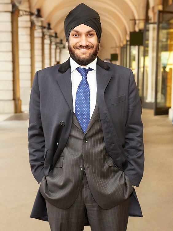 Portrait photograph of a grinning Indian Trader business man wearing a turban in Covent Garden London