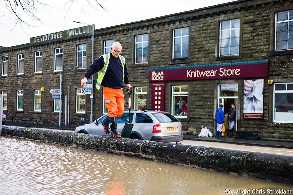 Hawick, Scotland, UK. 6th December 2015. A council worker clears up the streets of Hawick in the Borders after the River Teviot flooded overnight. Hawick is famous worldwide for its knitwear products.