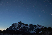 A meteor from the Perseid meteor shower streaks across the sky over Mount Shuksan in the North Cascades of Washington state. The Perseids are an annual meteor shower that occurs in August when Earth passes through the debris of Comet 109P/Swift-Tuttle. The meteors are comet debris burning up in the Earth's atmosphere.