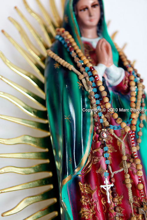 SHOT 12/6/10 2:47:33 PM - Rosaries hang from an Our Lady of Gudalupe figurine in a small roadside capilla near Santa Cruz, Mexico. Our Lady of Guadalupe (Spanish: Nuestra Señora de Guadalupe), also known as the Virgin of Guadalupe is a celebrated Catholic icon of the Virgin Mary. The Virgin of Guadalupe is Mexico's most popular religious and cultural image. Roadside capillas, or tiny chapels, in the Mexican state of Quintana Roo. The capillas are common along the roads and highways of Mexico which is heavily Catholic and are often dedicated to certain patron saints or to the memory of a loved one that has passed away. Often times they contain prayer candles, pictures, personal artifacts or notes. (Photo by Marc Piscotty / © 2010)
