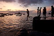 Kids jumping off the pier in Puerto Baquierzo Moreno, Island San Cristobal, Galapagos, Ecuador.