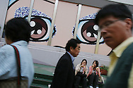 Pedestrains hurry past a billboard depicting a pair of 'manga' illustration type eyes,  in a Shinjuku street,  Tokyo, Japan.