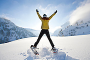 Erica Koltenuk greets the sun by jumping for joy while showshoeing in Utah's Wasatch Mountains.