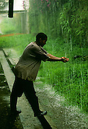 Man opens his hands to collect some water from the heavy rain in Roca (farm) Monte Cafe, one of the farms that still explore coffee plantation.
