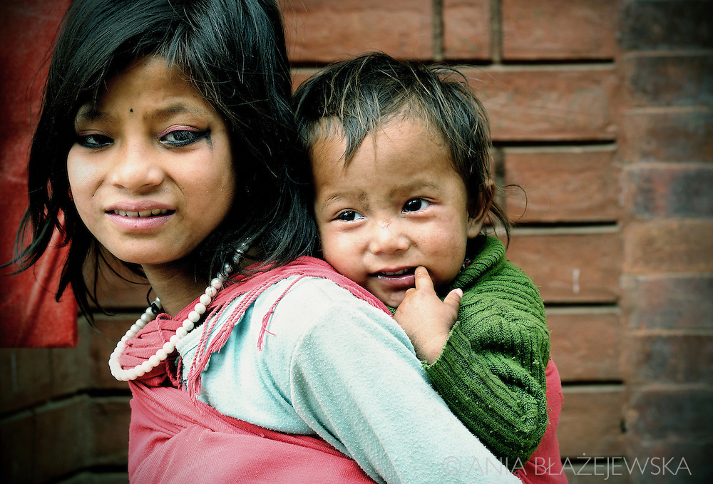 Nepal, Bhaktapur, Durbar Square. Girl carrying her younger brother.