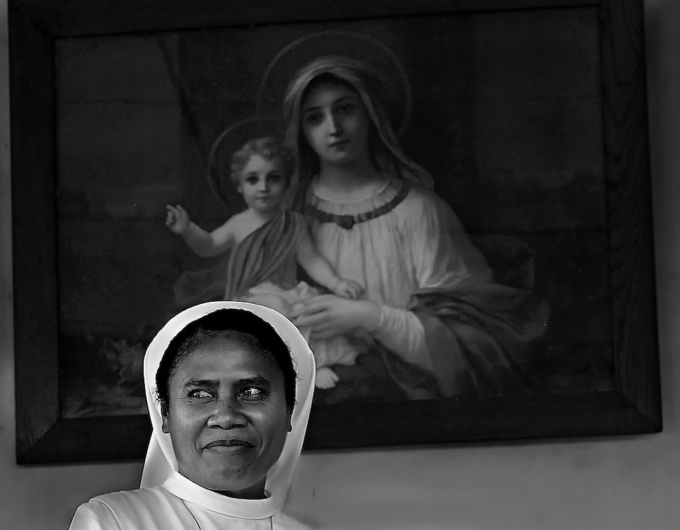 A nun on Flores Island in Indonesia in front of a painting of Mary and Jesus.