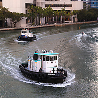 Two tugs cruise west on the Miami River near 3rd Avenue in downtown Miami, Florida