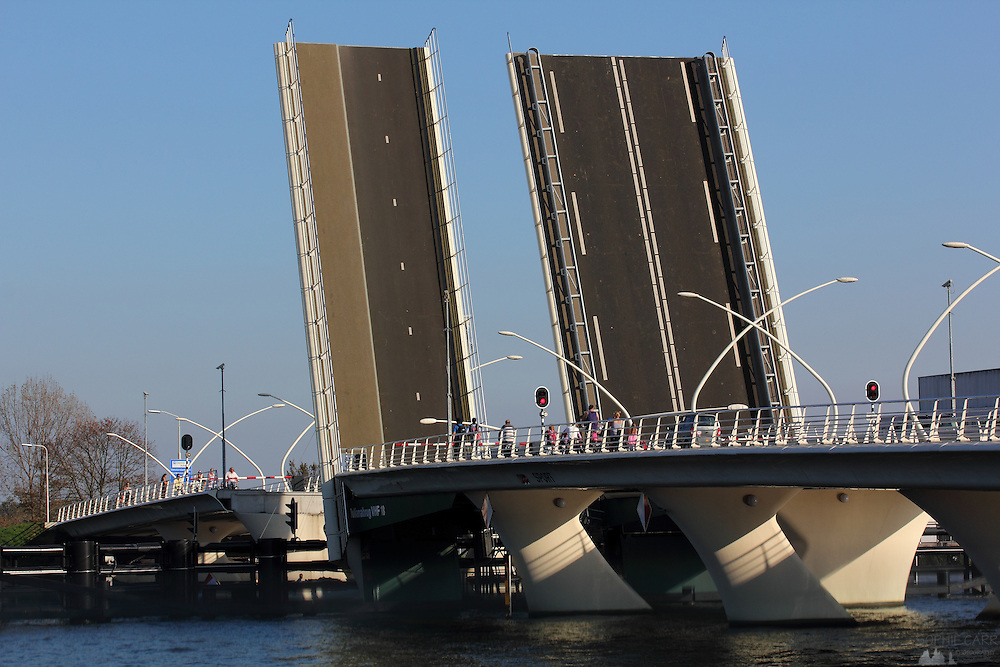 The Juliana Bridge at Zaanse Schans is opened up to allow a sailboat with a tall mast through, just north of Amsterdam