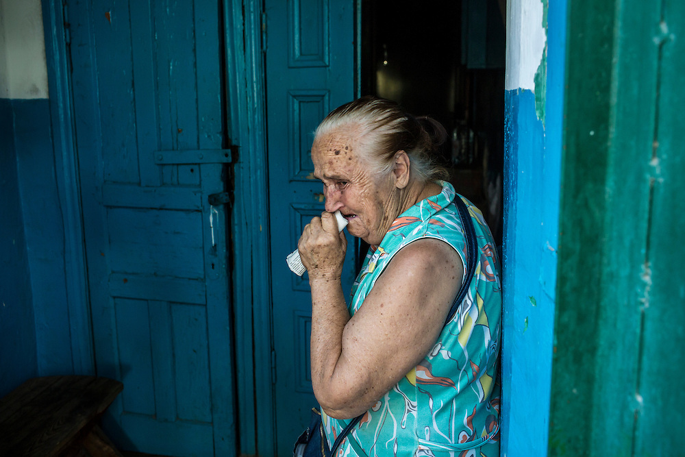 A resident of the Ploshchadka neighborhood, which has been heavily bombarded in recent days, becomes emotional after showing the basements shelter where she sleeps on Wednesday, July 30, 2014 in Donetsk, Ukraine.