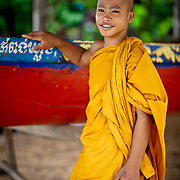 Monk poses by a traditional boat in Cambodia.