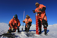 Marine chemists Agneta Fransson (Norwegian Polar Institute) and Melissa Chierici (Institute of Marine Research) sample seawater while ice physicist Sebastian Gerland (NPI)cores fjord ice to analyze ice and carbon cycle flux; Kongsfjord, Svalbard, Norway.