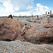 Kipushi, DRC. March 2009. Storm clouds building on the southwestern corner of the DRC, cast a dark light over these improvised quarries. The Congolese women admirably stylish even in these dire circumstances.