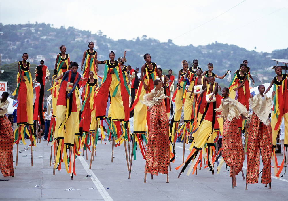 """Trinidad and Tobago """"MOKO JUMBIES: The Dancing Spirits of Trinidad"""".(Moko Jumbies, in full regalia, storm the stage at Queens Park Savannah as a section of the Legends band, who won the title Band Of The Year several times.).A photo essay about a stilt walking school in Cocorite, Trinidad..Dragon Glen de Souza founded the Keylemanjahro School of Art & Culture in 1986. The main purpose of the school is to keep children off the streets and away from drugs..He first taught dances like the Calypso, African dance and the jig with his former partner Cathy Ann Samuel.  Searching for other activities to engage the children in, he rediscovered the art of stilt-walking, a tradition known in West Africa as the Moko Jumbies , protectors of the villages and participants in religious ceremonies. The art was brought to Trinidad by the slave trade and soon forgotten..Today Dragon's school has over 100 members from age 4 and up..His 2 year old son Mutawakkil is probably the youngest Moko Jumbie ever. The stilts are made by Dragon and his students and can be as high as 12-15 feet. The children show their artistic talents mostly at the annual Carnival, which today is unthinkable without the presence of the Moko Jumbies. A band can have up to 80 children on stilts and they have won many of the prestigious prizes and trophies that are awarded by the National Carnival Commission. Designers like  Peter Minshall , Brian Mac Farlane and Laura Anderson Barbata create dazzling costumes for the school which are admired by thousands of  spectators. Besides stilt-walking the children learn the limbo dance, drumming, fire blowing and how to ride  unicycles..The school is situated in Cocorite, a suburb of Port of Spain, the capital of Trinidad and Tobago..all images © Stefan Falke"""