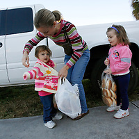 LEHIGH ACRES, FL -- January 23, 2009 -- Megan Brown of Lehigh Acres bundles up her daughters Kayley, 2, left, and Sydney, 4, after picking up free bread and pastries for her family at the bread line at Faith Lutheran Church in Lehigh Acres, Fla., on Friday, January 23, 2009.  Lehigh Acres has become a symbol for the fallen American Dream - with only two years separating itself from housing market boomtown to a current landscape of abandoned developments and struggling businesses.