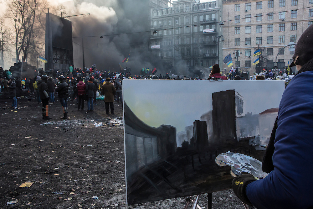 KIEV, UKRAINE - JANUARY 25: Artist Maksym Vegera paints a picure of the scene as anti-government protesters clash with police on Hrushevskoho Street near Dynamo stadium on January 25, 2014 in Kiev, Ukraine. After two months of primarily peaceful anti-government protests in the city center, new laws meant to end the protest movement have sparked violent clashes in recent days. (Photo by Brendan Hoffman/Getty Images) *** Local Caption ***