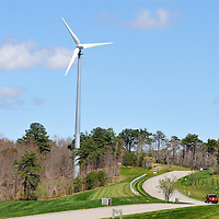 Wind turbine on a sunny blue sky day as part of landscape