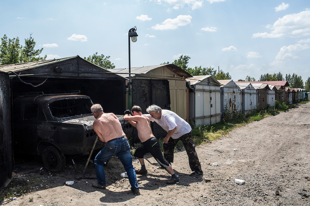 Residents of the Ploshchadka neighborhood, which has been heavily bombarded in recent days, move a burned car after a nearby garage was hit by a grad rocket on Wednesday, July 30, 2014 in Donetsk, Ukraine.