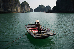 A vietnamese woman rows her barge in calm waters of Halong Bay, Vietnam, Southeast Asia