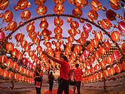 28 JANUARY 2017 - SAMUT PRAKAN, SAMUT PRAKAN, THAILAND: A woman walks through an archway of lanterns at the Chinese New Year Lantern Festival at the Tham Katanyu Foundation shrine in Samut Prakan, a suburb about 15 miles from Bangkok. More than 5,000 handmade lanterns imported from Taiwan are hung on the grounds of the shrine. Some of the lanterns are traditional Chinese lanterns, others are in the shapes of people or deities. There is also traditional Chinese entertainment, likes lion dances, at the festival.     PHOTO BY JACK KURTZ