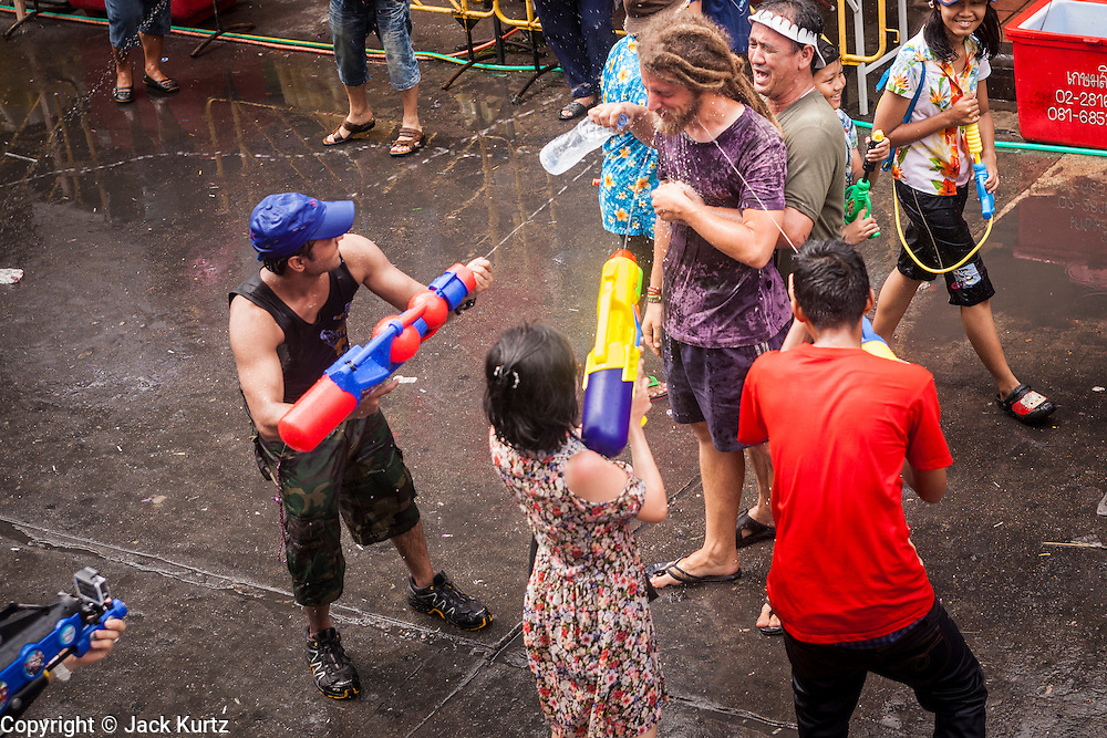 13 APRIL 2014 - BANGKOK, THAILAND: A tourist gets hit in a water fight on Khao San Road, Bangkok's backpacker district, on the first day of Songkran. Songkran is celebrated in Thailand as the traditional New Year's Day from 13 to 16 April. Songkran is in the hottest time of the year in Thailand, at the end of the dry season and provides an excuse for people to cool off in friendly water fights that take place throughout the country. Songkran has been a national holiday since 1940, when Thailand moved the first day of the year to January 1.   PHOTO BY JACK KURTZ
