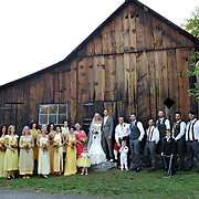 A wedding party in Coloma, California home of the California gold rush, pose for a portrait in front of an old barn.