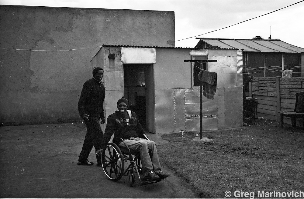Thokoza, 2009. South Africa. Linda Bayi, former Self Defence Unit member and Merchant Bonkosi Mazibuko, former commander of Slovo section Self Defence Unit. Paralysed by a bullet in his spine, while robbing a shop after 1994. Photo Greg Marinovich