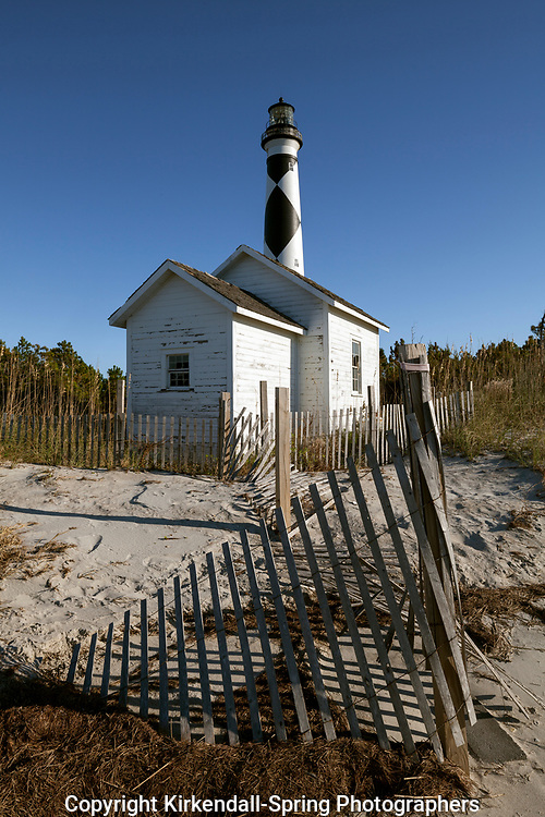 NC00878-00....NORTH CAROLINA -Sand fence, storage shed and Cape Lookout Lighthouse on the South Core Banks in Cape Lookout National Seashore.