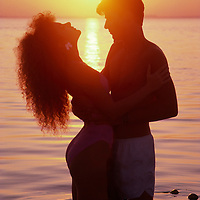 Young couple standing in shallow calm water  silhouetted by a golden sunset.