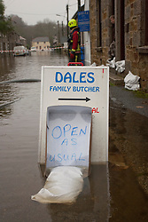 © Licensed to London News Pictures. 22/12/2012. Helston, UK. Sign outside butchers shop on St Johns Road which was flooded by River Cober when it burst its banks. The Environment Agency issued a Severe flood warning for the River Cober. Photo credit : Ashley Hugo/LNP