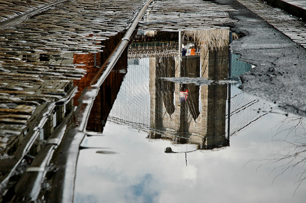Reflection of the Brooklyn bridge in a puddle on a street of DUMBO, Brooklyn, New York, 2008.