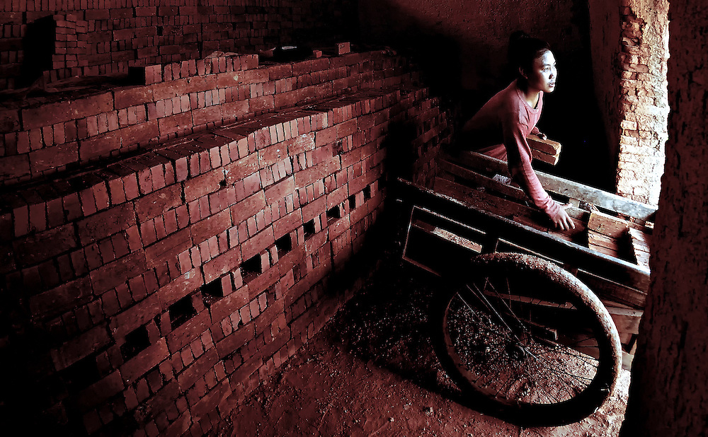 A girl loading a trolley of bricks in a kiln in Sainyabuli province, Laos.