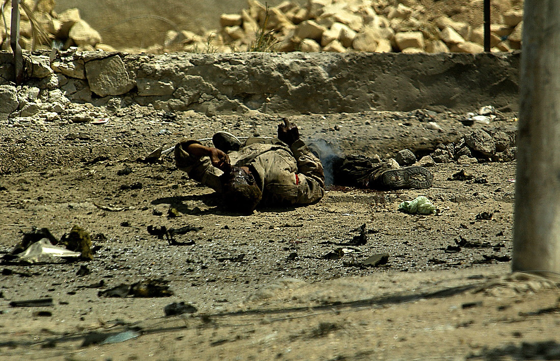 An injured Iraqi man lays in the street after a suicide car bomb explosion at an intersection in Tameem, Ramadi, Iraq on August 10, 2006. The soldiers from Bravo Company 2-6 Infantry, Task Force 1-35 from Baumholder Germany, were performing a routine patrol at an intersection in Tameem, a suburb of Ar Ramadi when a suicide car bomb exploded about twenty five meters in front of the patrol. Initial reports indicated that two were killed (one civilian and the bomber) and four were wounded (one Iraqi Police Officer and three civilians). Immediately after the explosion, Soldiers of Bravo Company cordoned off the area, treated and evacuated the wounded and maintained security until an Explosive Ordinance Disposal team (EOD) arrived to clear the area.  One civilian died of wounds at the treatment facility.  While EOD was on scene, the patrol took small arms fire from outside of the cordon.  EOD recovered one 110mm artillery round and three 115mm rounds that were believed to be connected with detonation wires from the dashboard of the vehicle. — © TSgt Jeremy Lock/