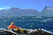 Alaska. A salmon fisherman prepares to fish for salmon in windy conditions near Kodiak island.