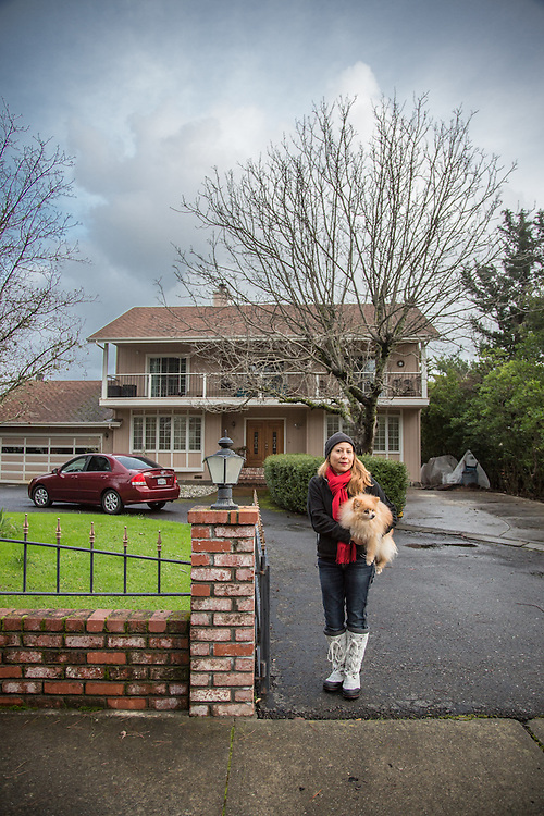 """Buddy and I moved into this house about a year ago...I have three roommates.""""    Massage/Hypno Theropist Liza Xavier stands with her dog, Buddy, in front of her home on a blustery afternoon in Calistoga."""