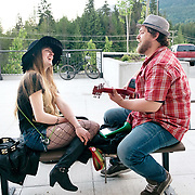 Street musicians sing a duet in front of a shopping centre.  Whistler BC, Canada