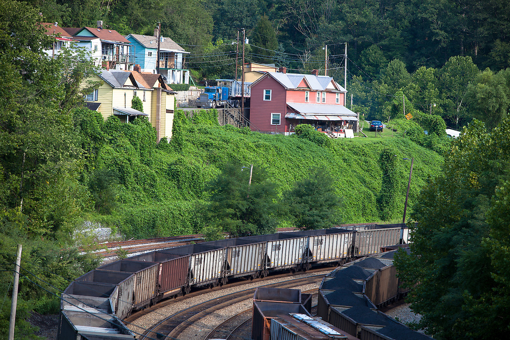 In the heart of West Virginia coal country, near Welch, WV, houses on the steep bluffs overlook the railroad yard below, while a semi truck hauling coal heads for the tipple.